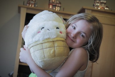 little girl holding a stuff animal Christmas present
